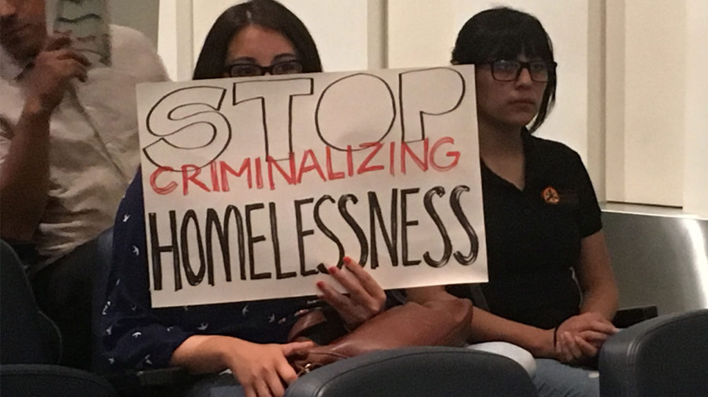"""Photo of an audience member holding a sign that reads """"Stop Criminalizing Homelessness"""""""