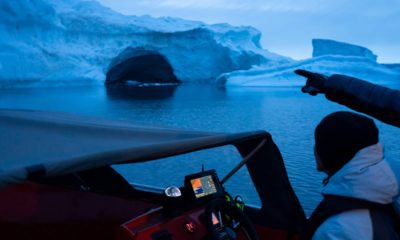 Photo of a boat navigating at night next to a large iceberg in Greenland