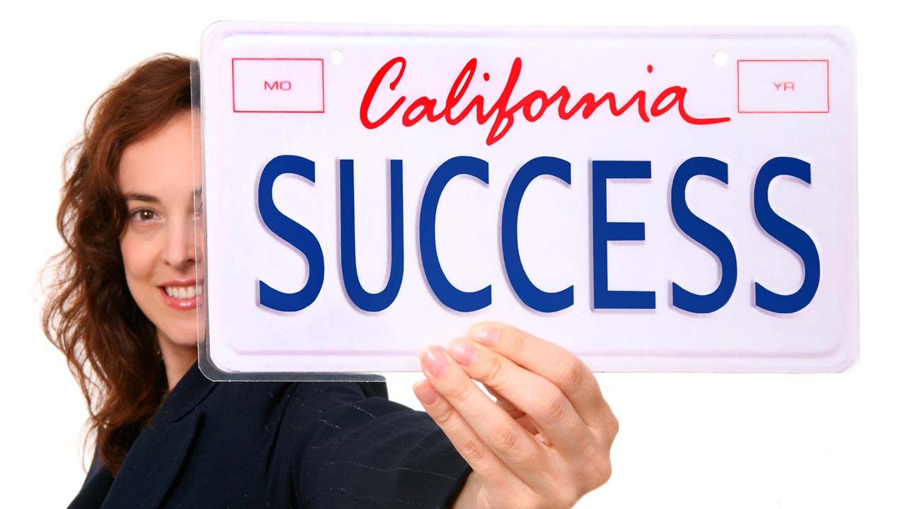 """Photo of a woman holding a California license plate that says """"Success"""""""
