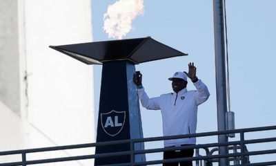 Photo of Cliff Branch lighting a memorial flame in honor of Al Davis.