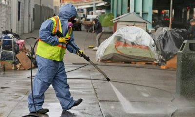 Photo of a city worker cleaning the sidewalk by a tent city