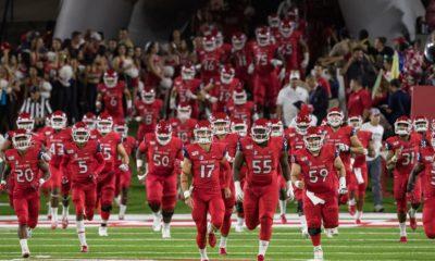 Photo of Fresno State football players running onto the field at Bulldog Stadium