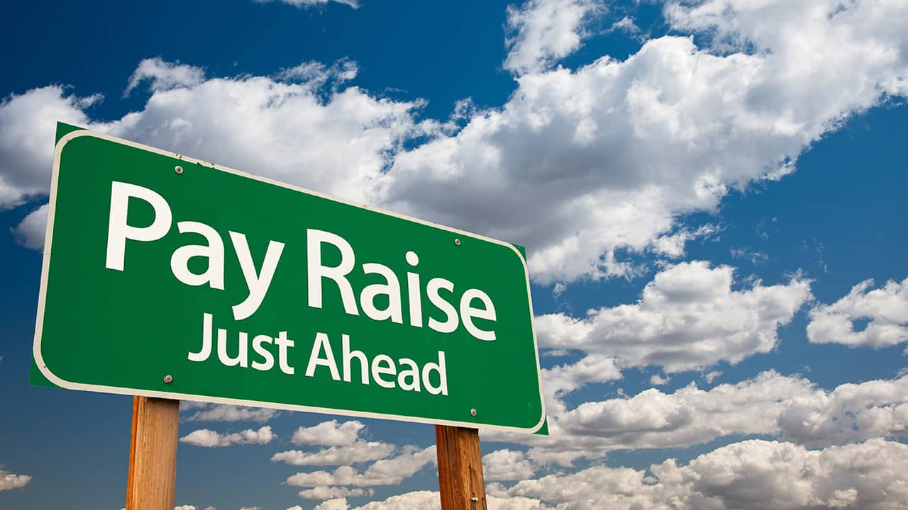 Composite image of a pay raise ahead sign and blue skies