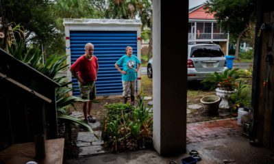 Photo of couple standing outside their home before evacuating
