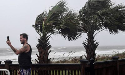 Photo of a man taking photos of waves crashing in Myrtle Beach