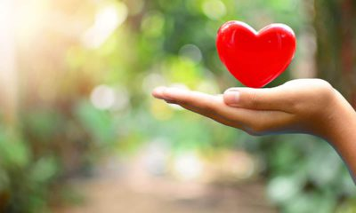Photo of a hand holding a decorative heart signifying generosity