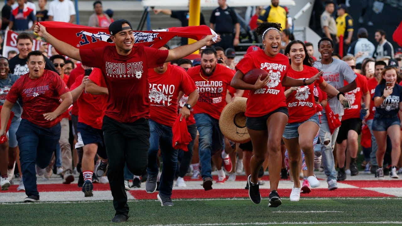Photo of Fresno State students running onto the football field
