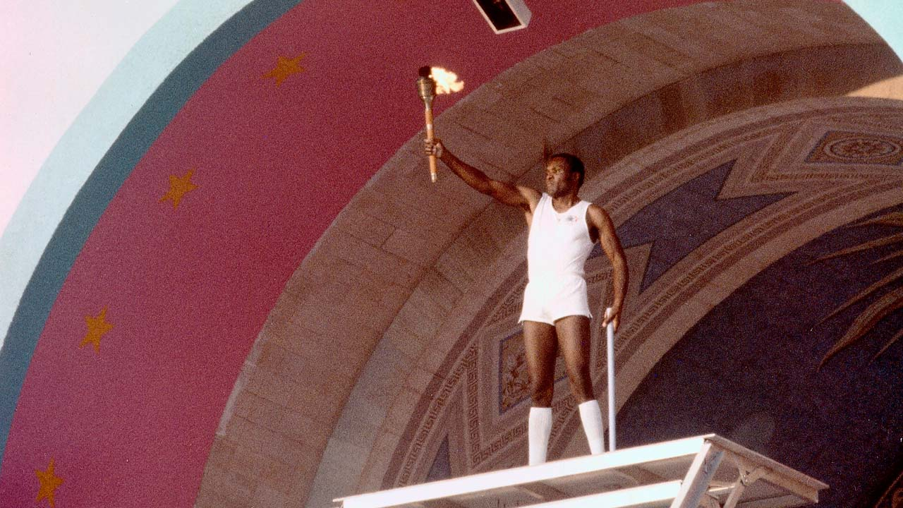 Photo of Rafer Johnson holding the Olympic torch in 1984