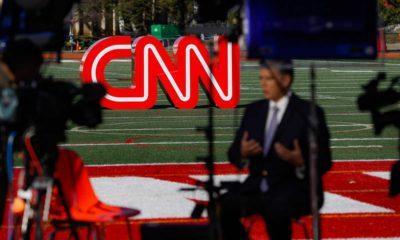 Photo of a journalist recording a video near a CNN sign
