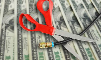 Composite image of money, scissors and cable TV cord