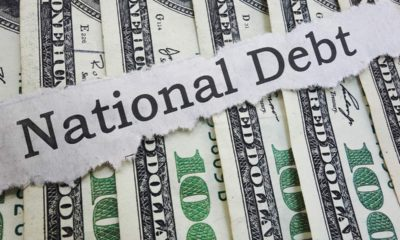 """Photo of money and """"national debt"""" on a ripped piece of paper"""