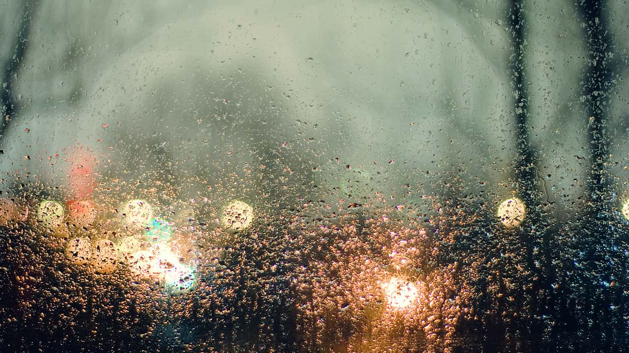 photo of rain and lights seen through a window