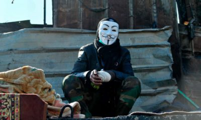 Photo of a protester wearing a Guy Fawkes mask