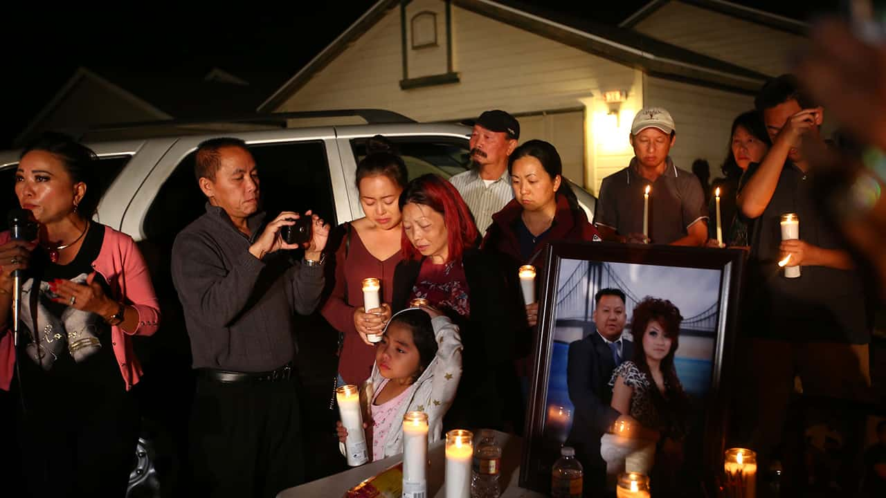 Photo of the wife and young daughter of shooting victim Kou Xiong standing among a crowd during a candle light vigil