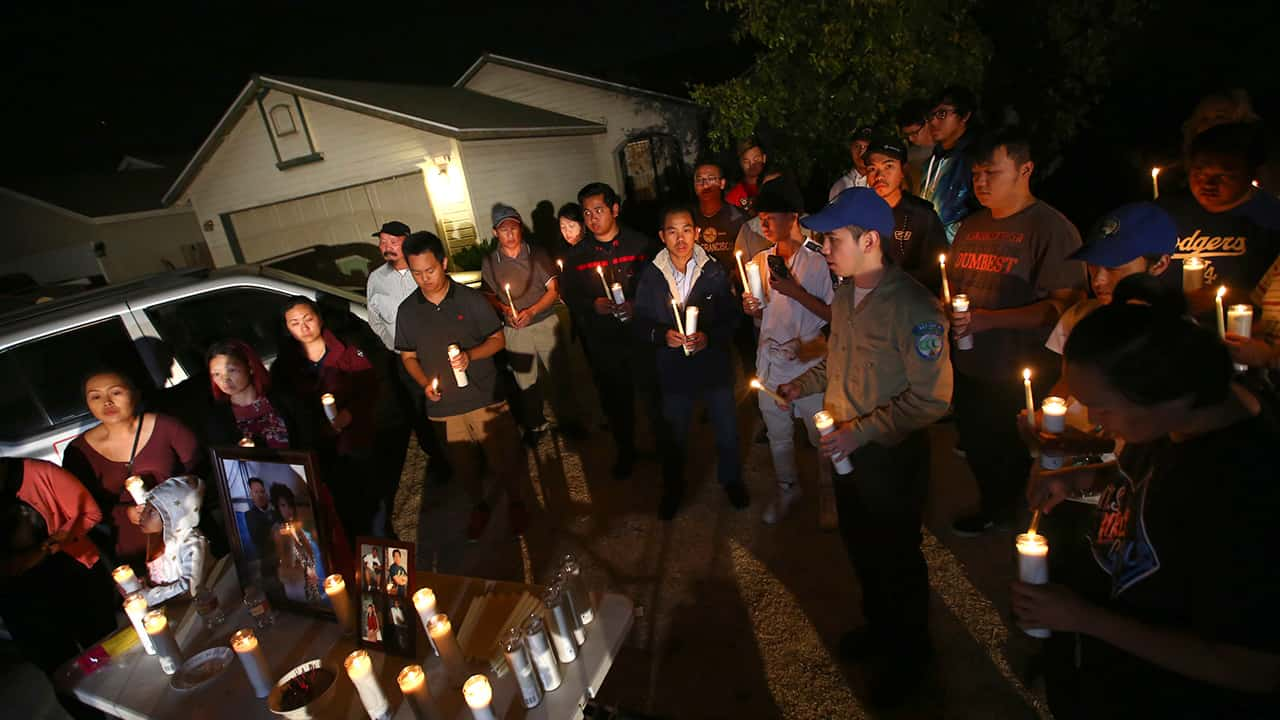 """In this photo taken Monday, Nov. 18, 2019, friends and family of shooting victim Kou Xiong gather in front of his home for a candle light vigil in Fresno, Calif. A close-knit Hmong community was in shock after gunmen burst into a California backyard gathering and shot 10 men, killing four. """"We are right now just trying to figure out what to do, what are the next steps. How do we heal, how do we know what's going on,"""" said Bobby Bliatout, a community leader. (Larry Valenzuela/The Fresno Bee via AP)"""