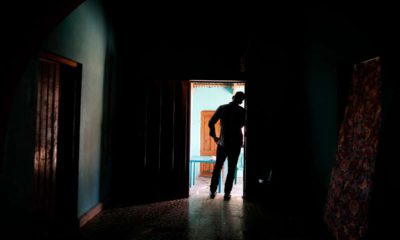 Photo of Honduran father standing at his home