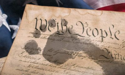 Composite photo of footprints trampling the U.S. Constitution