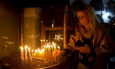 Photo of a visitor lighting candles