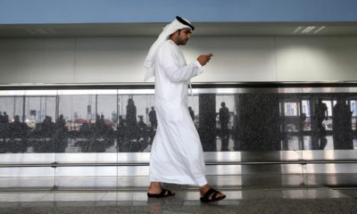 Photo of a worker looking at his phone at the airport in Dubai