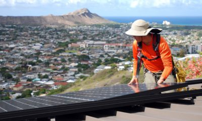 Photo of Dane Hew Len, lead installer for RevoluSun, placing a solar panel on a roof