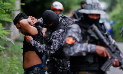 Photo of police frisking a man in El Salvador