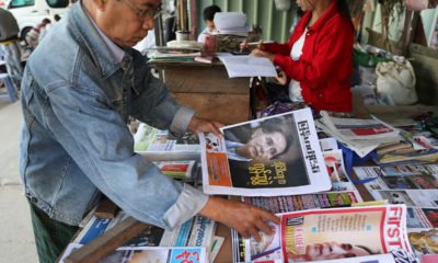 Photo of a man looking through newspapers