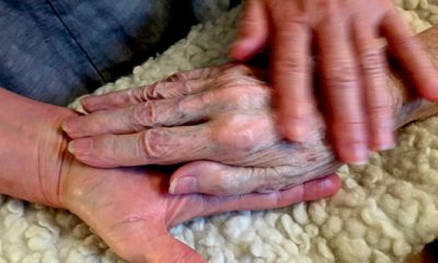 Photo of Allison Beach holding the hand of her ailing mother Kathryne Beach inside her home in Hinesburg, Vt.