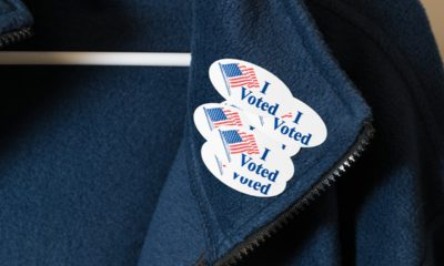 """Photo of a jacket with multiple """"I Voted"""" stickers"""