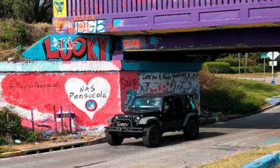 Photo of a vehicle driving by a tribute to the victims of the Naval Air Station Pensacola