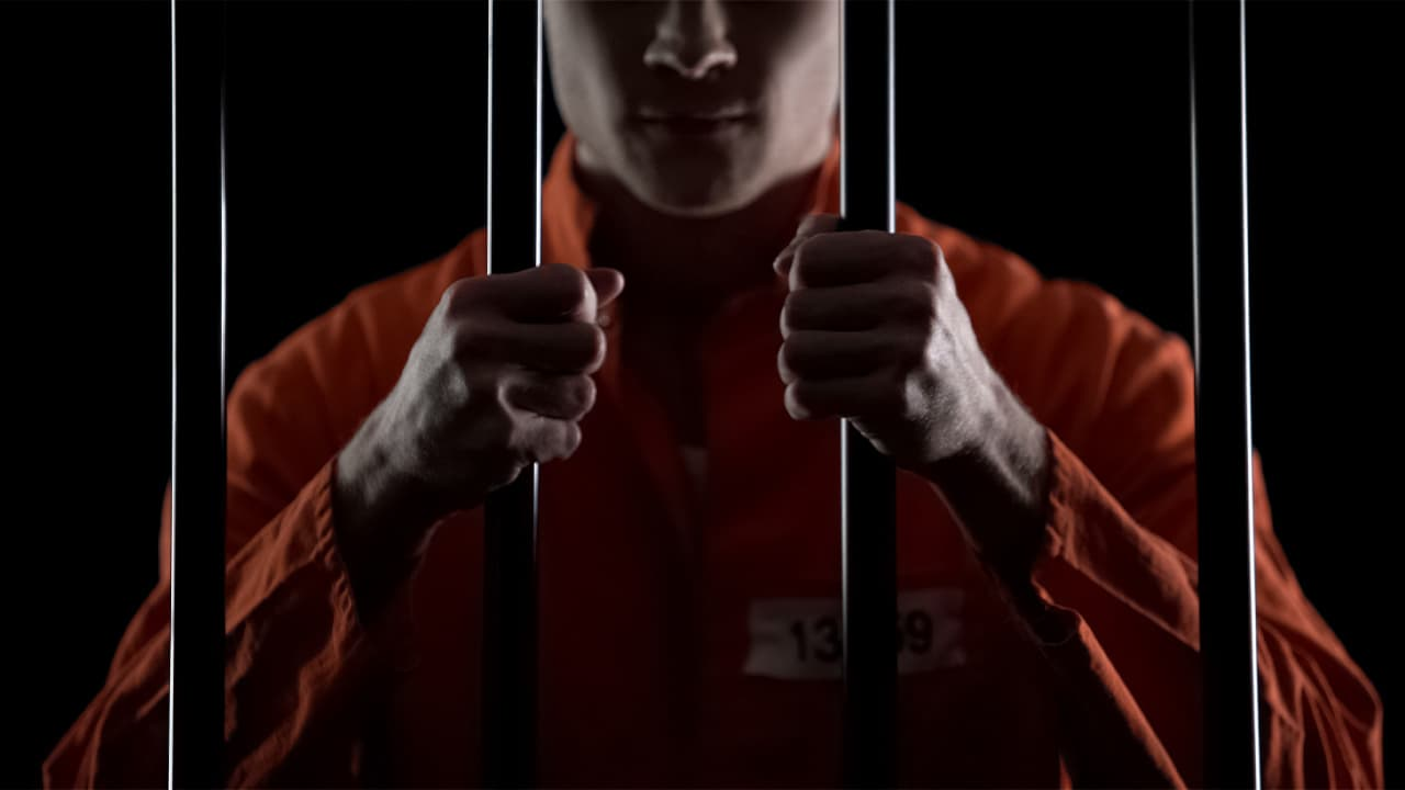 Photo of a man in an orange jumpsuit behind prison bars