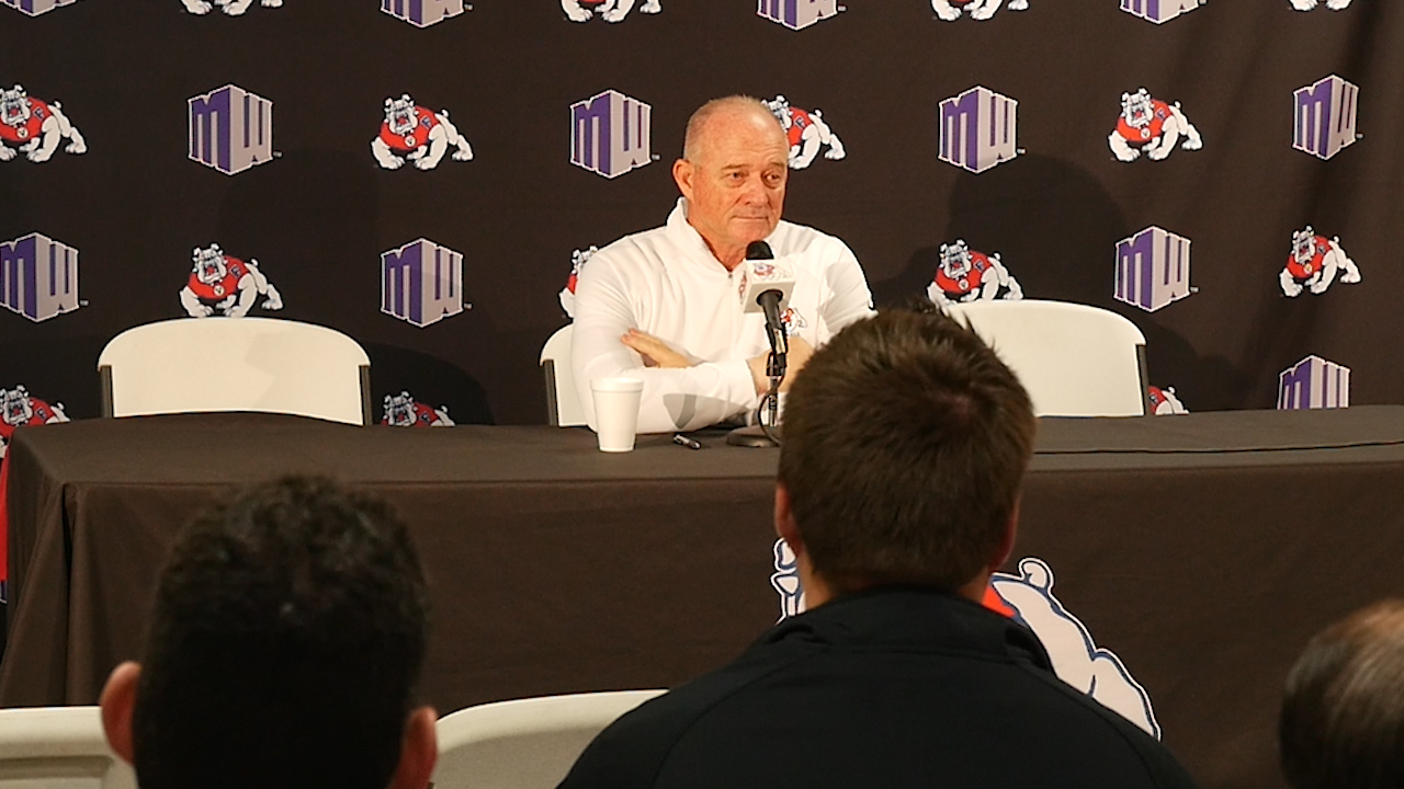 Photo of Jeff Tedford sitting at a table and talking to the media.