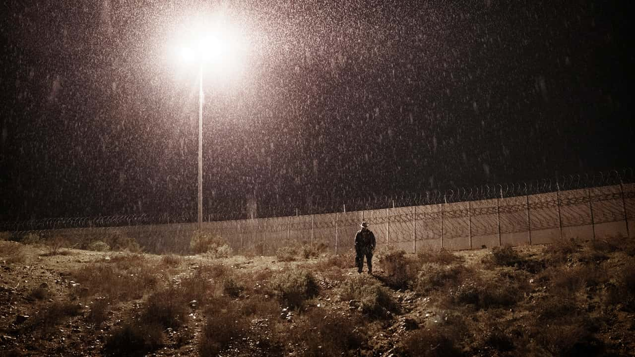 Photo of a U.S. Border Protection officer standing in the rain