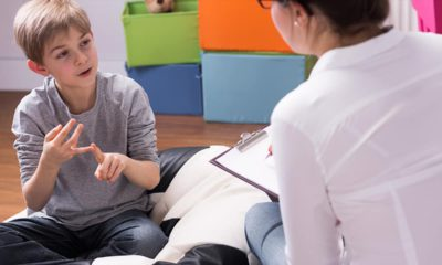 Photo of a young boy talking to a psychologist