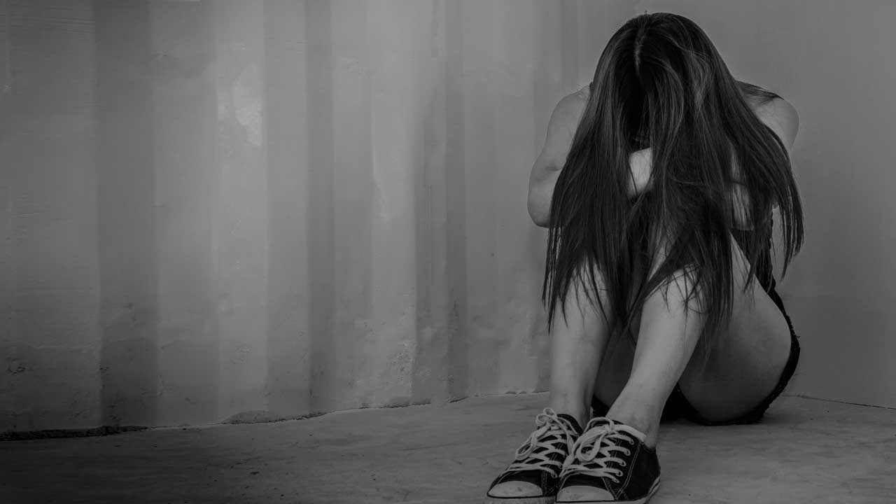 Photo of a sad young woman sitting in a room on the floor