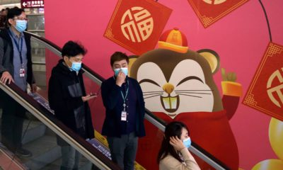 Photo of people wearing face masks as they ride an escalator in China