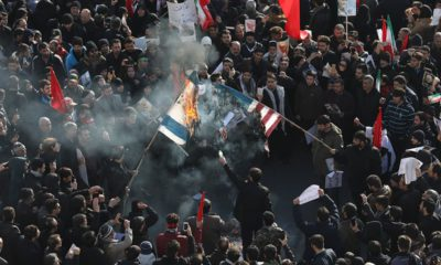 Photo of mourners burning mock flags of the U.S. and Israel during a funeral ceremony for Iranian Gen. Qassem Soleimani