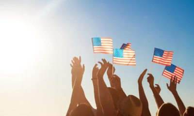 Photo of a blue sky and people holding American flags