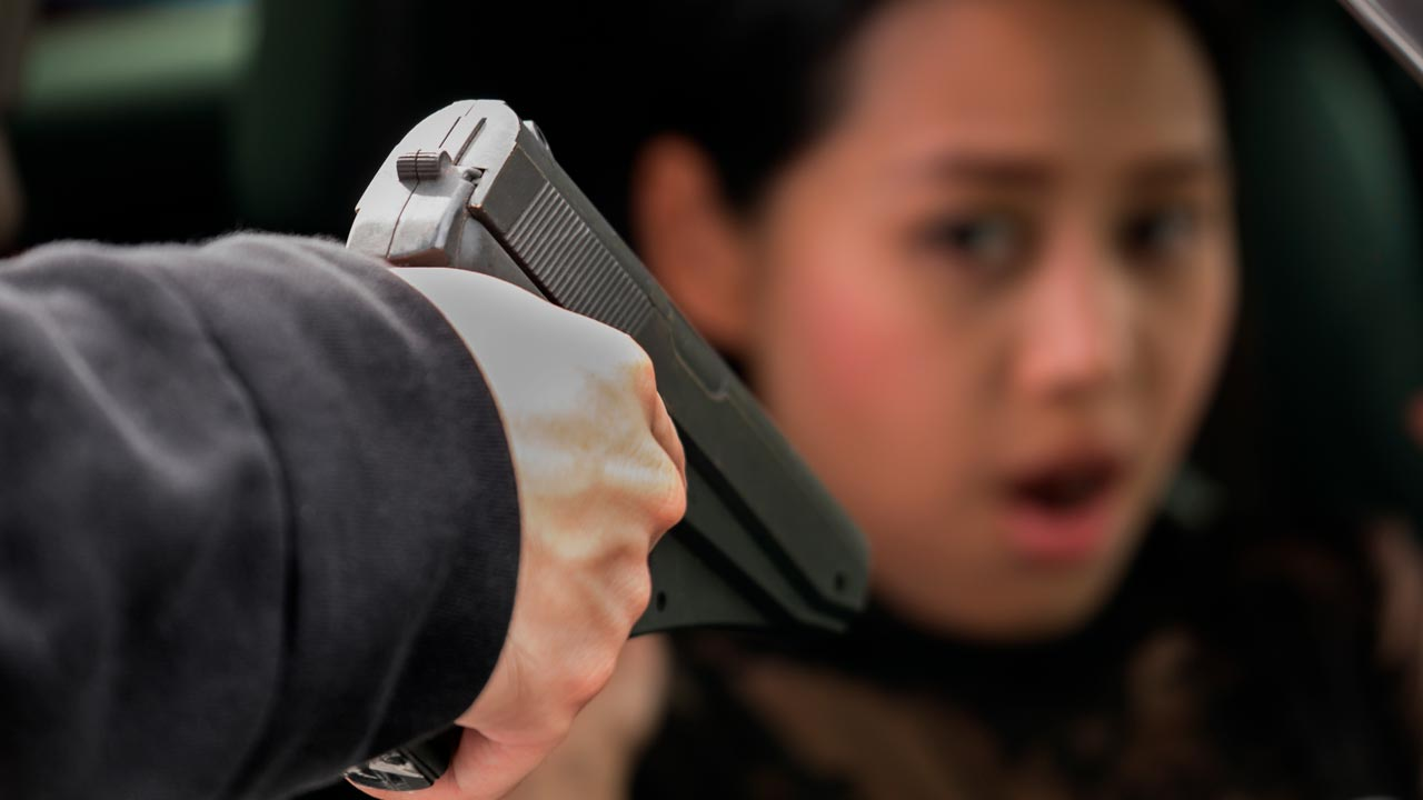 Staged photo of a gang member pointing a gun at a woman in a car
