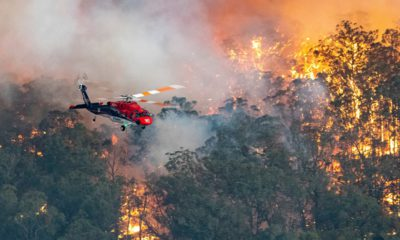 Photo of a helicopter and wildfires burning in Australia