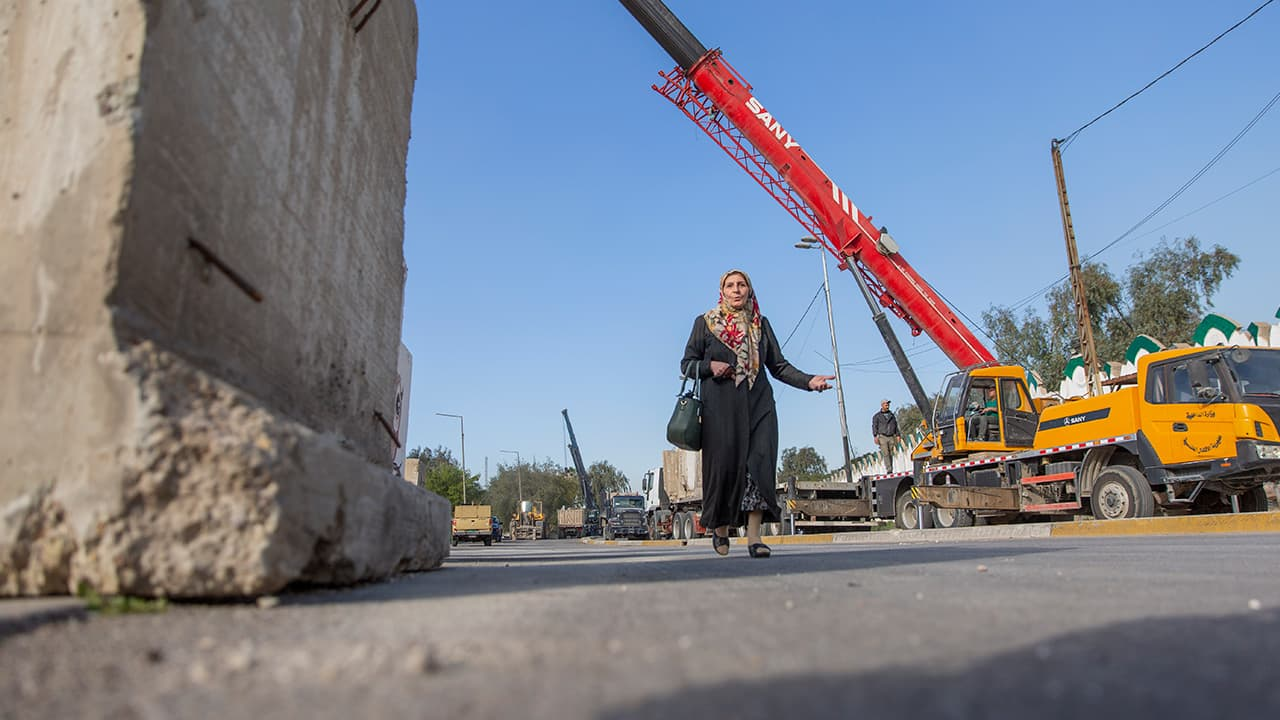 Photo of a woman passing by Iraqi security forces