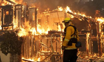 Photo of a firefighter monitoring a house burning in Santa Rosa, Calif.