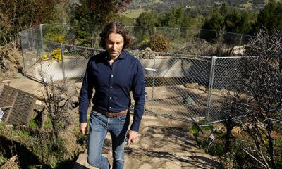 Photo of Jason Meeks walking through the remains of his hime in Santa Rosa, Calif.