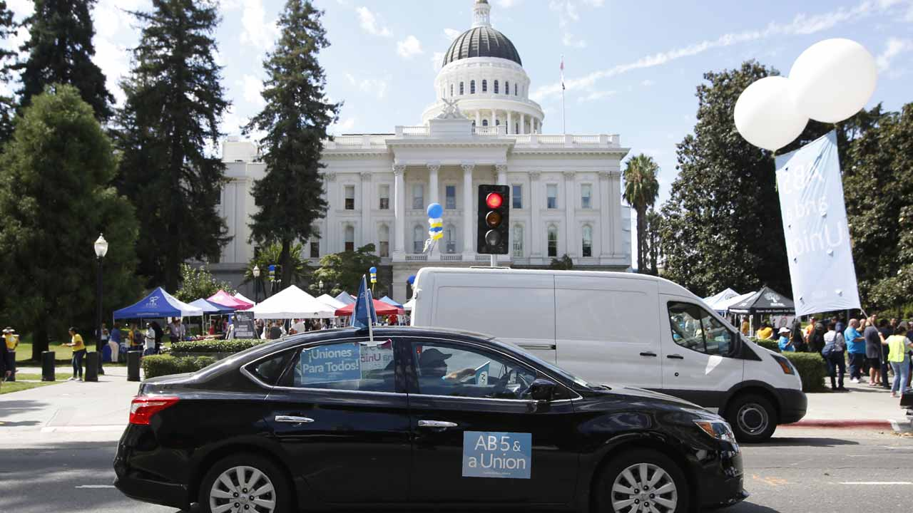 Photo of a car with banners supporting AB 5, the California law reclassifying independent contractors