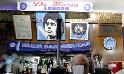 Photo of a bar tender preparing an espresso coffee inside the Bar Nilo where a makeshift shrine of soccer legend and former Napoli player Diego Armando Maradona is displayed