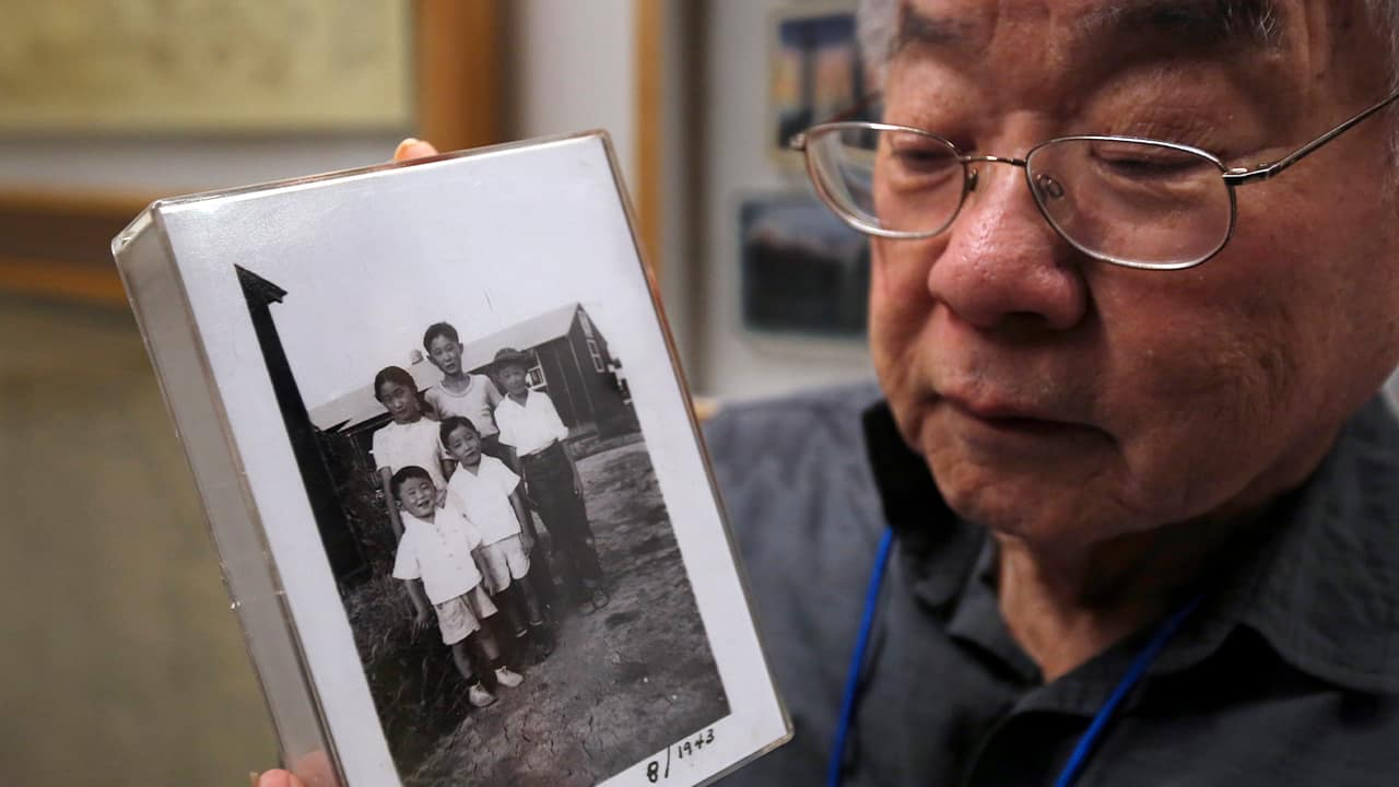 Photo of Les Ouchida holding a 1943 photo of himself, front row, center, and his siblings taken at the internment camp his family was moved to