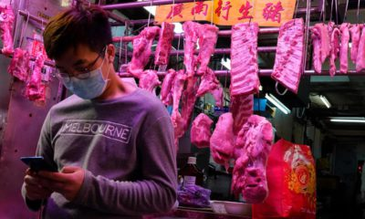 Photo of a man wearing a face mask in front of a meat booth in Hong Kong