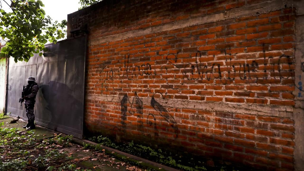 Photo of a police guard next to a graffiti wall in El Salvador