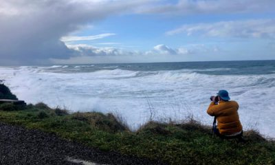 Photo of a man photographing waves crashing onto the cliffs at Rodea Point in Lincoln County, Ore.