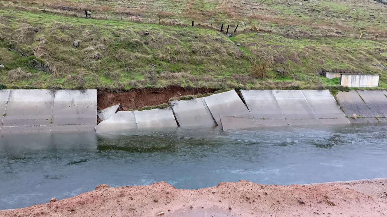 Photo of a canal with a damaged wall
