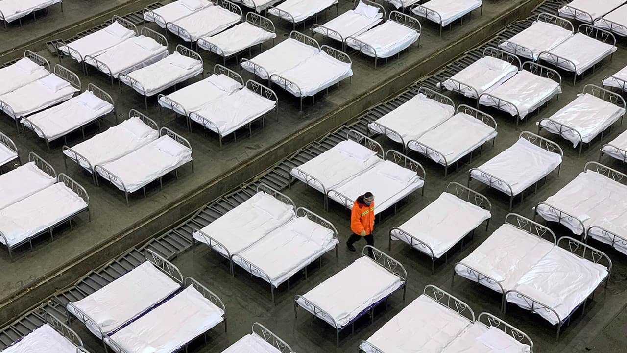 Photo of workers arranging beds in a convention center